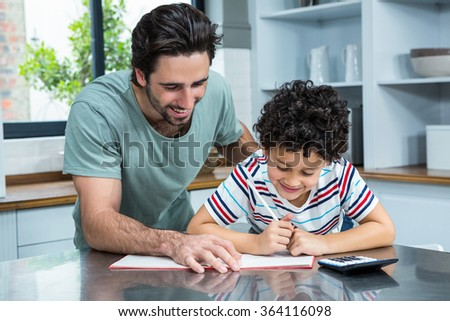 Kind father helping his son doing homework in the kitchen - stock photo