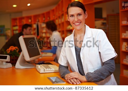 Kind female pharmacist behind counter in a pharmacy