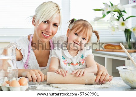 Kind mother and child baking cookies in the kitchen - stock photo