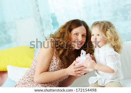 Kind mother giving her daughter small present in giftbox - stock photo