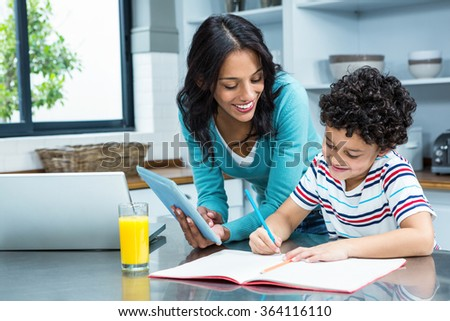 Kind mother helping her son doing homework in kitchen while using tablet and laptop