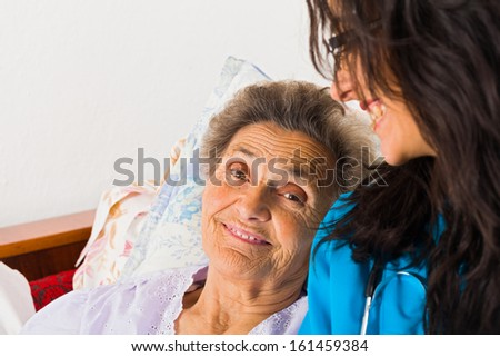Kind nurse easing elderly lady's days in nursing home with care help and joy. - stock photo