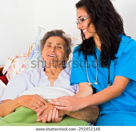 Kind nurse easing elderly lady's days in nursing home with care help and joy.