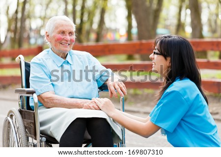 Kind nurse holding elderly lady's hand while chatting with her. - stock photo