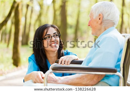 Kind nurse laughing with elderly patient in wheelchair. - stock photo
