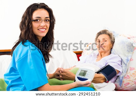 Kind nurse measuring elderly patient's blood pressure at home. - stock photo