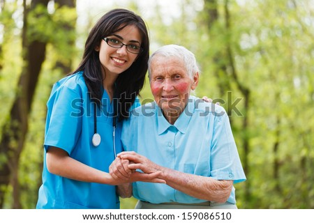 Kind nurse together with elderly woman in the hospital's garden. - stock photo