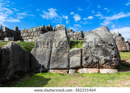 Kind of a piece of a wall of stones of great size and different shape, folded tightly and without cement against the blue sky and green grass near Saksayuman, Peru