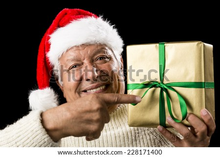 Kind old man with astute smile gesturing with his right index finger at a wrapped golden present raised to his shoulder in his left hand. Reminder for gift giving. Green bowknot. Red Santa Claus cap. - stock photo
