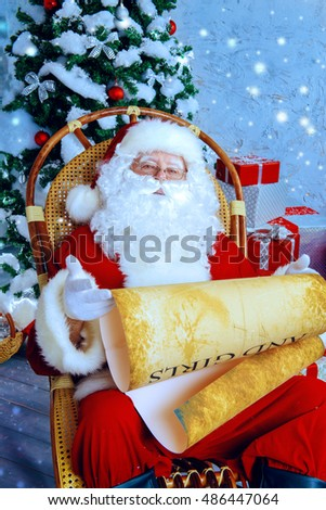 Kind Santa Claus sits in a snow-covered Christmas room and reads the scroll. Santa's mail, wish list.