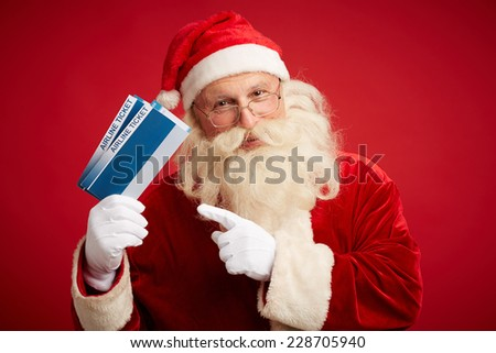 Kind Santa Claus with two airline tickets looking at camera over red background - stock photo