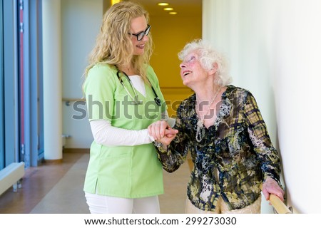 Kind Therapist Woman Assisting an Elderly Patient with Special Needs Walking at the Corridor Inside the Hospital - stock photo