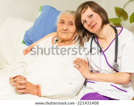 kind young female nurse caring for a very old femaile patient,in hospital - stock photo