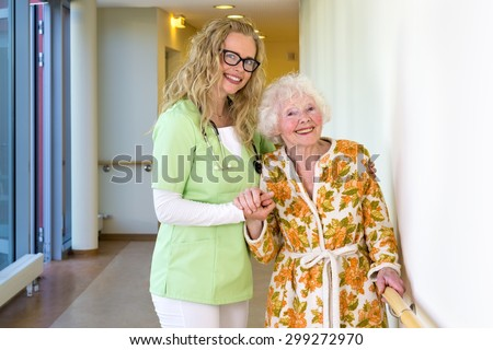 Kind Young Female Therapist and her Elderly Woman Patient Smiling at the Camera at the Corridor Inside the Hospital. - stock photo