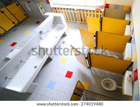 kindergarten bathroom with washbasins and cabins without children - stock photo