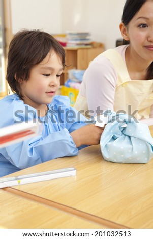 Kindergarten boys opening the lunch box