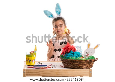 Kindergarten girl showing yellow Easter egg isolated on white background - stock photo