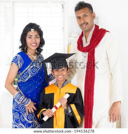 Kindergarten graduation. Asian Indian family, parents and child on kinder graduate day. - stock photo