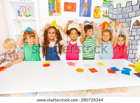 Kindergarten group of little kids, boys and girls diverse looking holding cardboard shapes by the table in the kindergarten with decoration and drawings on background