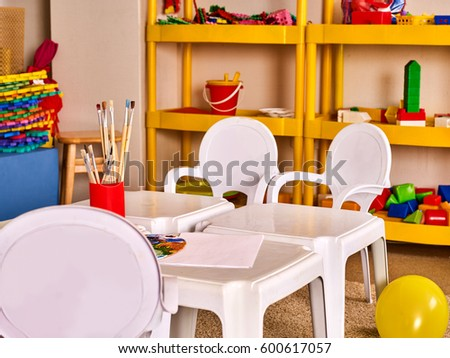 kids at classroom table. kindergarten tables and chairs in interior decoration shelves for toys. preschool class waiting kids. kids at classroom table s
