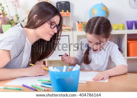 Kindergarten Teacher And Cute Little Girl Drawing Lessons - stock photo