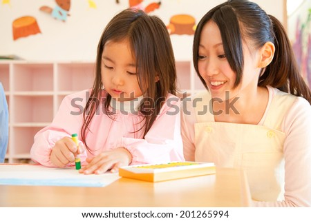 Kindergarten teachers watching the kindergarten girls to enjoy drawing