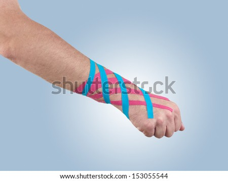 Kinesio tex tape therapeutic treatment of the wrist. Its purpose is to detonisize the muscle to reduce pain and also used for prevention and treatment in competitive sports.  - stock photo