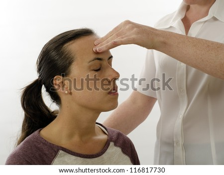 Kinesiologist or physiotherapist treating Neuro vascular holding - emotional stress release - stock photo