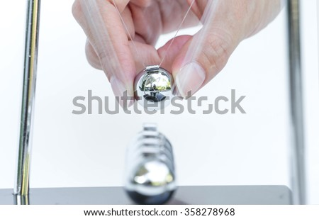 kinetic ball with hand on white background - stock photo