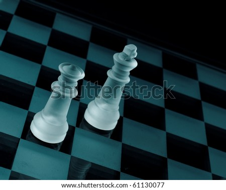 King and Queen Chess Pieces on Glass Chessboard