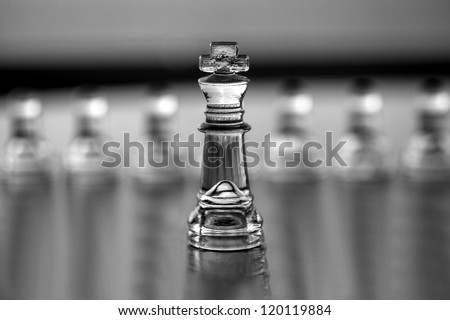King chess piece (pawns blurred in background) as a business concept series -  leadership, mentor, CEO, coaching, business guru, consultant. With text  or copy space for business card design.  - stock photo