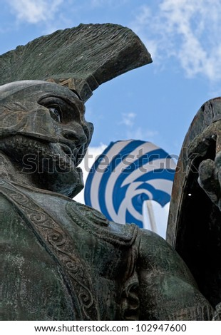 King Leonidas statue with Greek Flag in background. - stock photo