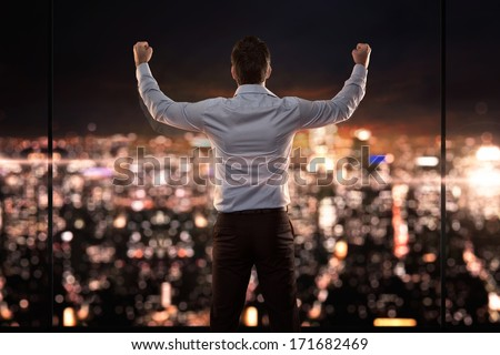King of the world, young successful businessman in front of the city at night