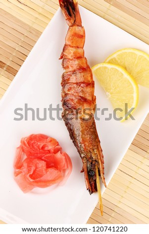 king prawn skewers on plate with ginger and lemon