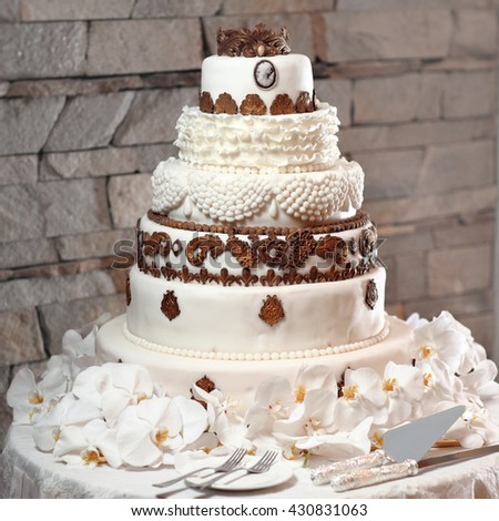King size round tiered white wedding cake with bronze pattern