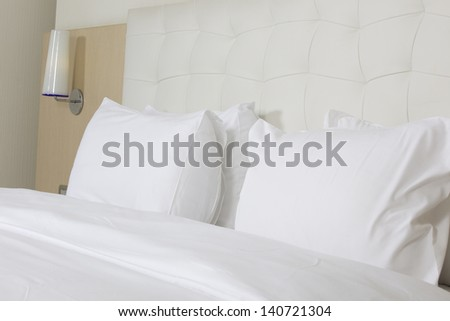 King sized bed in a luxury hotel room - stock photo
