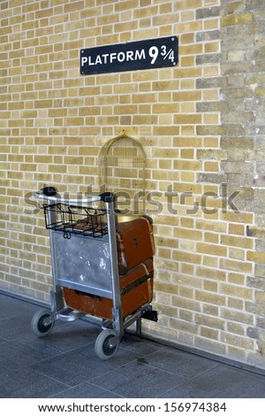Kings Cross station wall visited by fans of Harry Potter to photograph sign for platform nine and three quarters with trolley  - stock photo