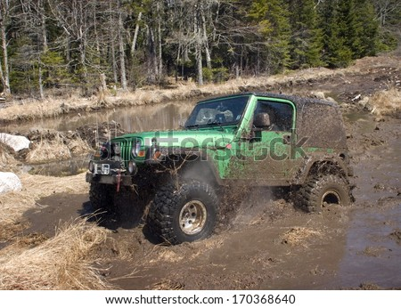 KINGSTON, NOVA SCOTIA, CANADA, APRIL 17, 2008:  A Jeep blasts through a mud bog without getting stuck.
