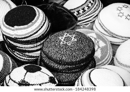 Kippah with Magen David (Star of David) and other Yarmulkes for sale at the market in Jerusalem (Israel). Closeup. Selective focus on the upper corner of the Magen David. Jewish background. Aged photo - stock photo