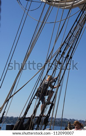 KIRKLAND, WASHINGTON - SEP 1:Crew descends the rigging of the Lady Washington   during a mock sea battle as part of Labor Day festivities on Sep 1, 2012 near Kirkland , Washington...