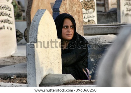 Kirkuk,Iraq - December August 25,2005 : Thousands of people lost their lives in the war in Iraq.Family waiting at the grave of your child.