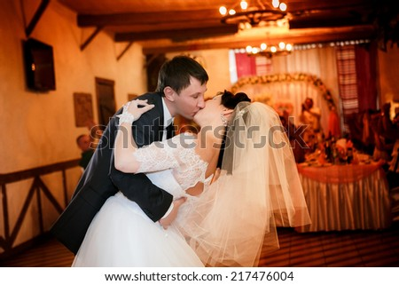 Kiss and dance young bride and groom in banqueting hall - stock photo