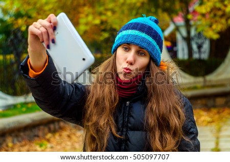 Kiss for selfie on the street in autumn weather and bright colors