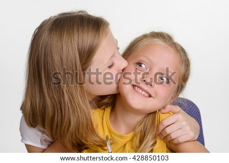 Kiss from the elder sister is precious. Young girl is happy to have such lovely sibling. Love and care in family. Close-up portrait.