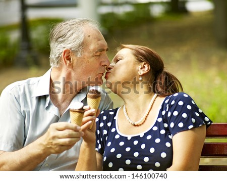 Kiss happy old couple eating ice-cream outdoor. - stock photo