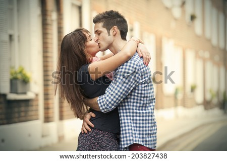 kiss of couple on street of Chelsea in London - stock photo