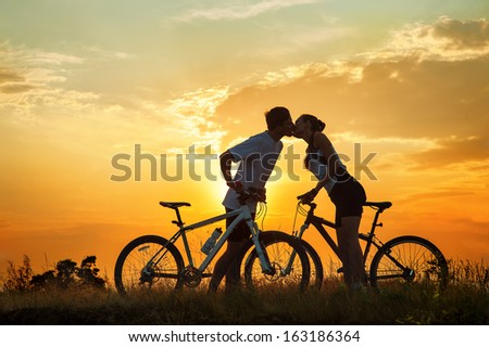 Kiss of romantic young couple on bicycles against sunset - stock photo