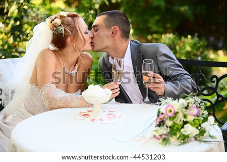 Kiss of the groom and the bride holding glasses with champagne