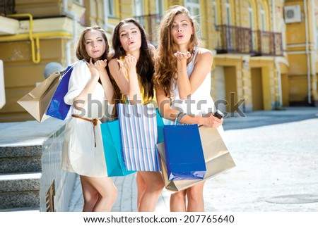 Kiss. Three attractive young girl holding shopping bags while standing near the store and look at the camera. Girls laughing and smiling at the camera outdoors
