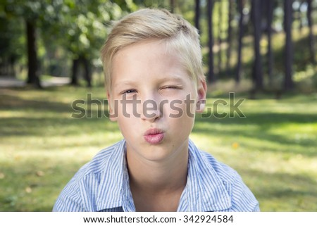 Kissing boy sits on green grass in forest. Concept of happy thoughts and positive emotions.
